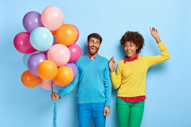 Happy young couple at a party posing with balloons