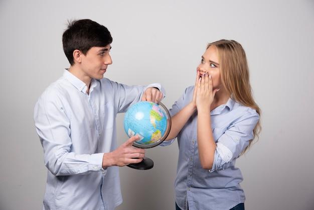 Felice giovane coppia che pianifica la destinazione dell'anniversario con in mano un globo.