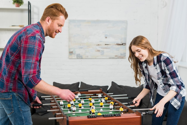 Happy young couple playing the football table soccer game at home