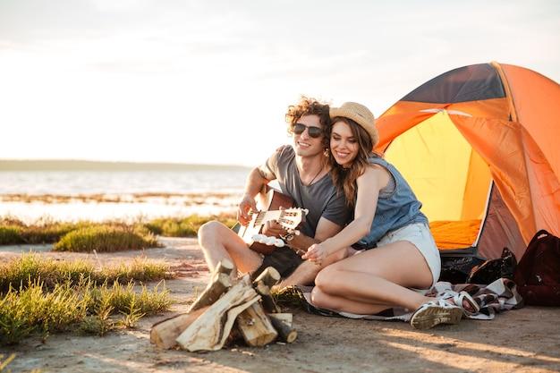 Счастливая молодая пара играет на гитаре и жарит зефир на костре вместе