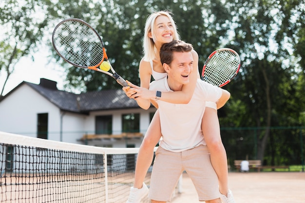 Happy young couple playing tennis