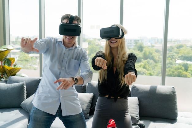 Счастливая молодая пара, играя в видеоигры с очками виртуальной реальности у себя дома.