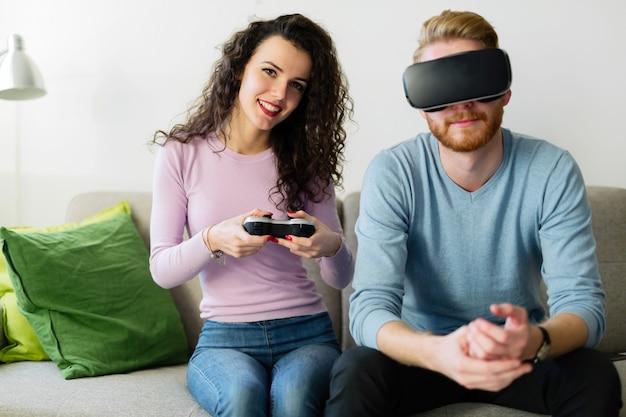 집에서 가상 현실 헤드셋으로 비디오 게임을 하는 행복한 젊은 커플