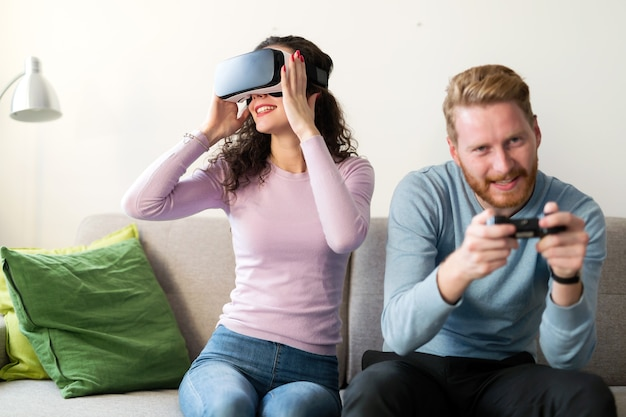 Happy young couple playing video games with virtual reality headsets at home