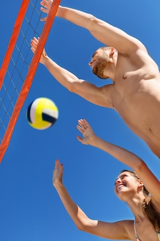 Happy young  couple playing volleyball