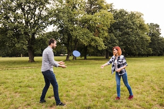 Happy young couple playing with flying disc in the garden