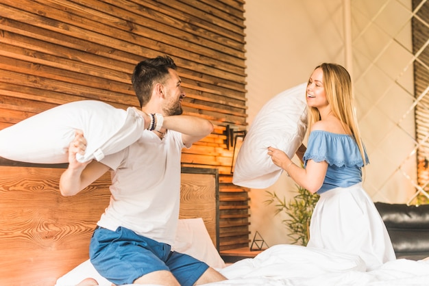 Happy young couple playing with pillows on bed