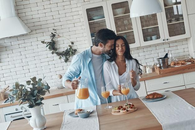 행복한 젊은 커플이 함께 아침 식사를 준비하고 부엌에서 시간을 보내는 동안 웃고