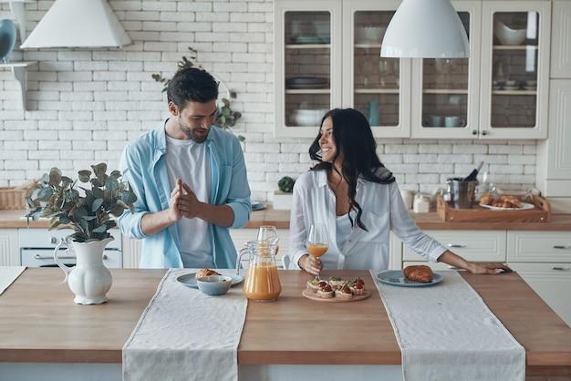 국내 부엌에서 시간을 보내면서 함께 아침 식사를 준비하는 행복한 젊은 부부