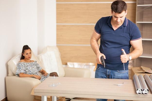 彼らが引っ越してきたときに自己組立家具を組み立てる幸せな若いカップル