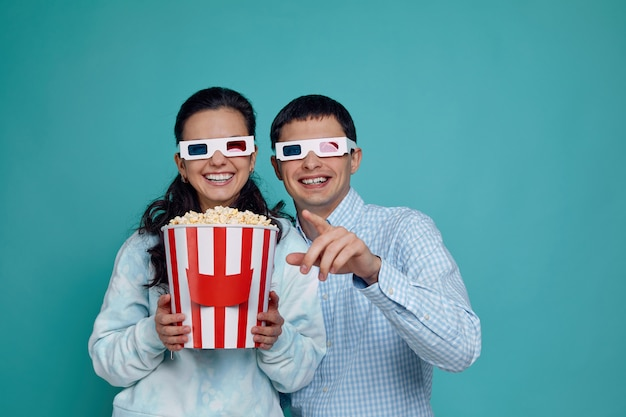 Happy young couple in red-blue 3d glasses eating popcorn from bucket while watching a movie isolated on blue
