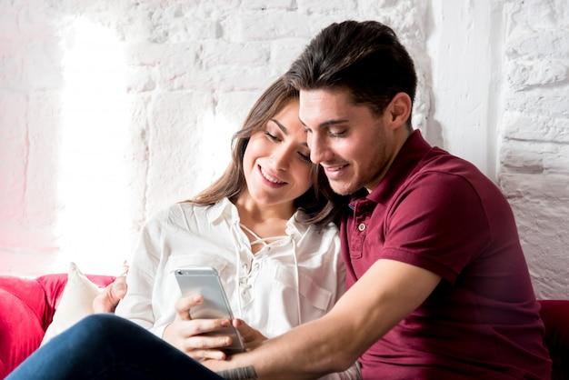 幸せな若いカップル、自宅でリラックスした携帯電話