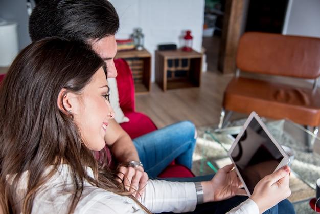 幸せな若いカップルが家でタベットでリラックス