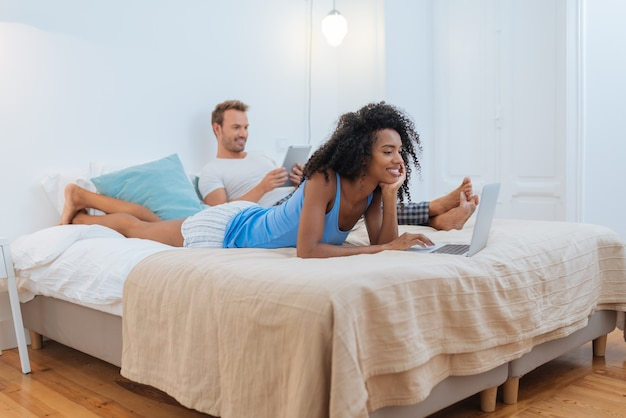 Happy young couple relaxed at home lying down in bed on the tablet and computer