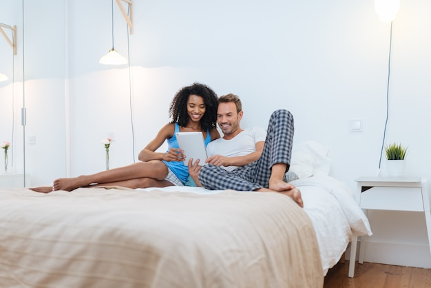 Happy young couple relaxed at home lying down in bed on the tablet