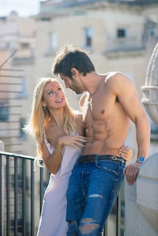 Happy young couple relaxing on balcony at home, tender