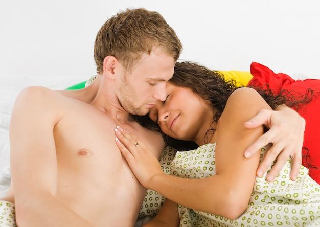カラフルな枕の周りのベッドでリラックスして幸せな若いカップル