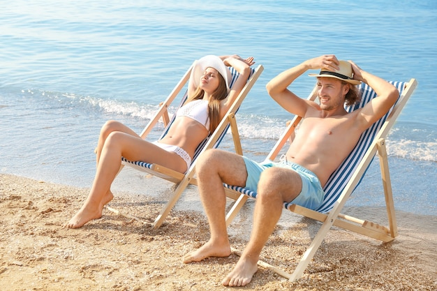 海のリゾートで休んでいる幸せな若いカップル