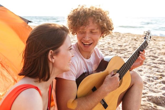 Счастливая молодая пара, отдыхая вместе на пляже, в кемпинге, играя на гитаре