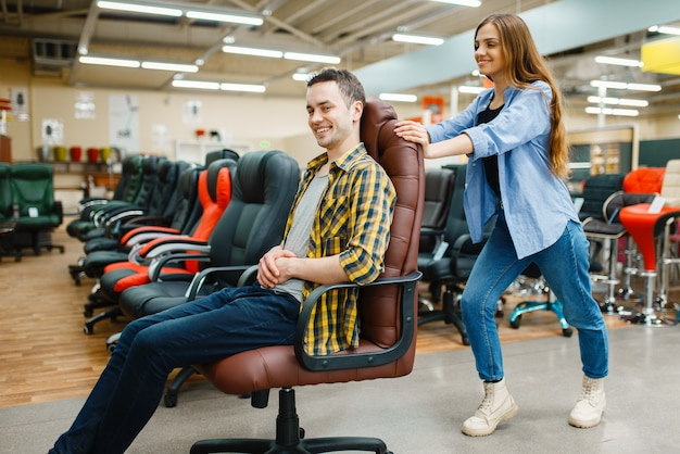 Happy young couple rides on office chair in furniture store showroom. man and woman looking samples for bedroom in shop, husband and wife buys goods for modern home interior