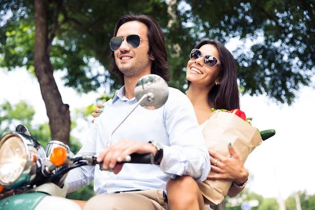 Счастливая молодая пара на скутере