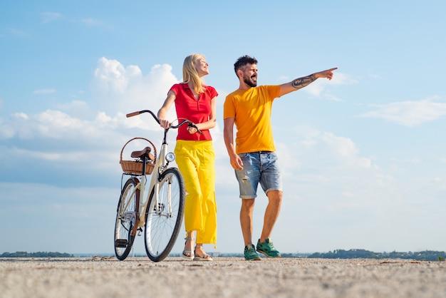 자전거를 타고 행복 한 젊은 커플. 퇴직. 여행을 즐기는 젊은 라이더. 동안