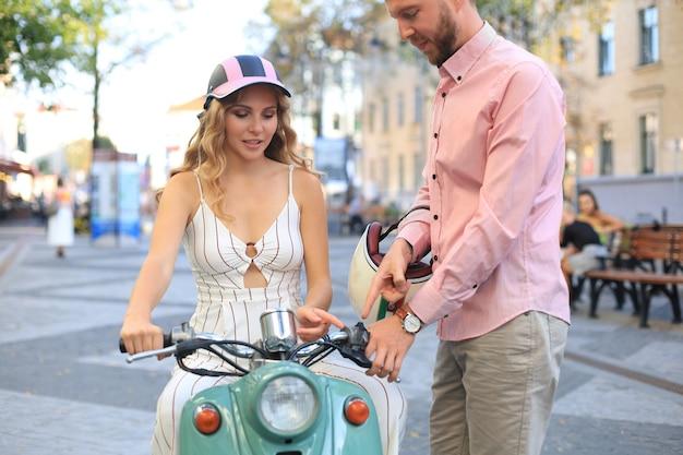 町でスクーターに乗って幸せな若いカップル。ハンサムな男と若い女性が旅行します。冒険と休暇のコンセプト。