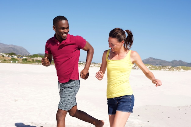 Happy young couple running on beach