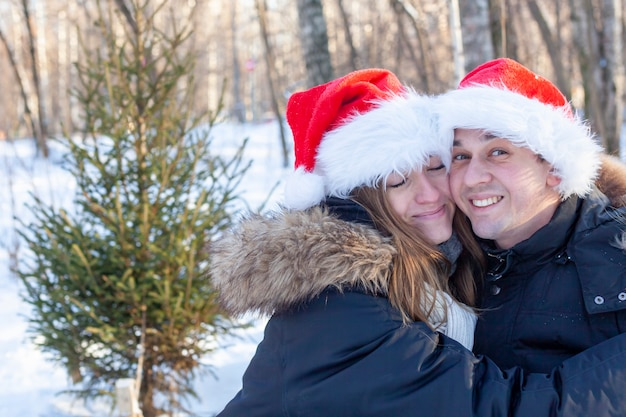 Happy young couple in santa claus hats smile and laugh on the background of a winter forest with a christmas tree.