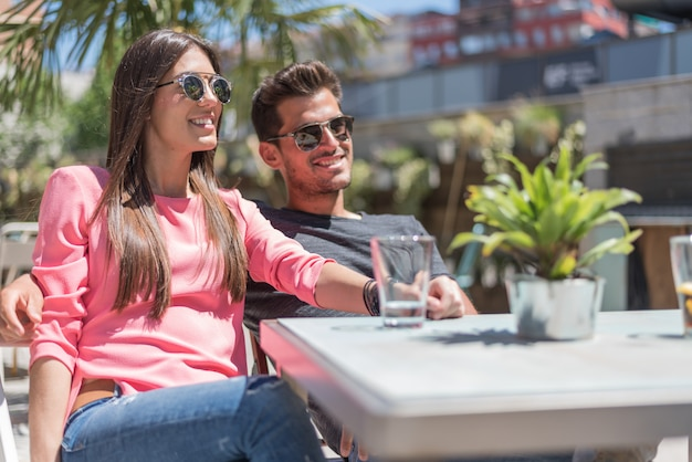 Happy young couple seating relaxed in a restaurant terrace