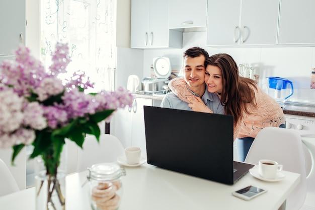 Счастливая молодая пара самостоятельно изолированы дома с помощью ноутбука, пить кофе