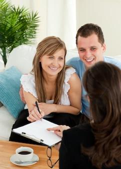 Счастливая молодая пара, подписания контракта, сидя в гостиной