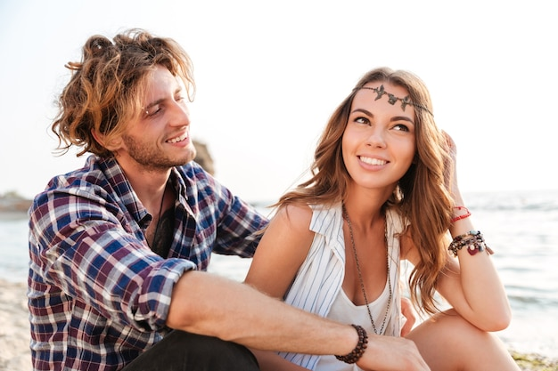 夏のビーチで座って笑って幸せな若いカップル