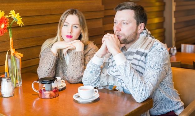 행복 한 젊은 커플 카페에 앉아 신중 하 게 거리를 들여다