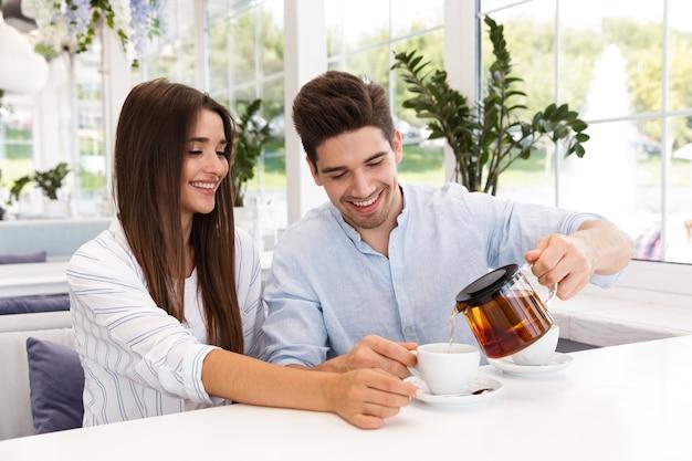 행복 한 젊은 커플 카페 테이블에 앉아 차를 마시는