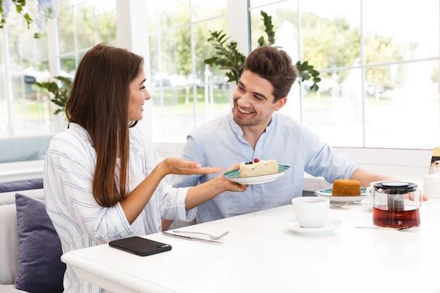 행복 한 젊은 커플 카페 테이블에 앉아 점심을 먹고, 이야기