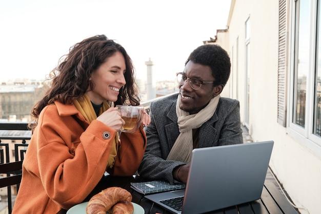 Счастливая молодая пара сидит за столом, используя ноутбук и пьет чай вместе в кафе