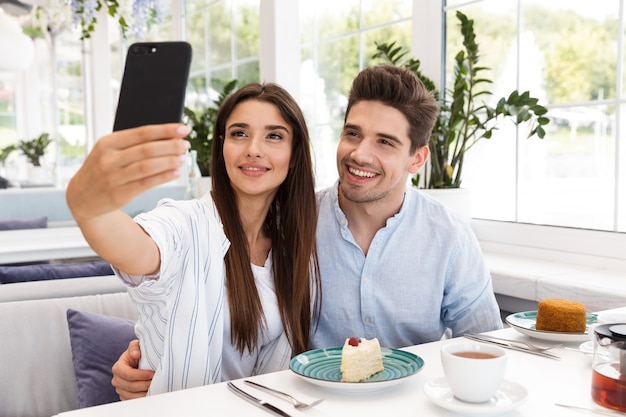 Happy young couple sitting at the cafe table, having lunch, taking a selfie