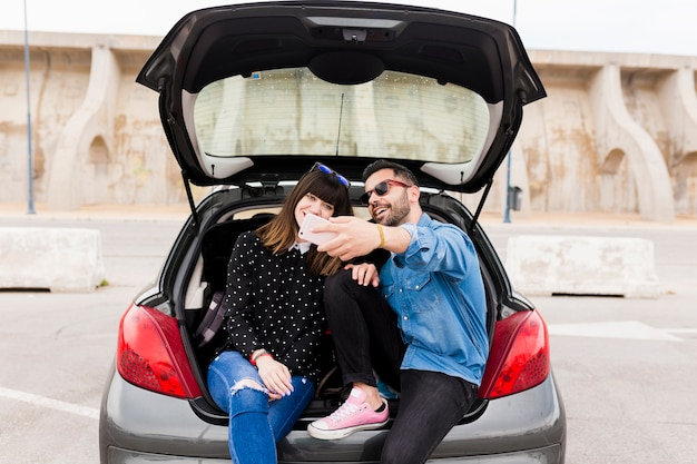 Happy young couple sitting in car trunk taking self portrait