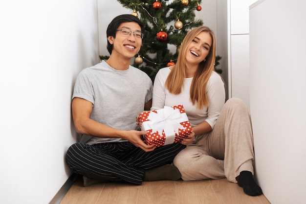 Happy young couple, sitting at the christmas tree, holding gift box at home
