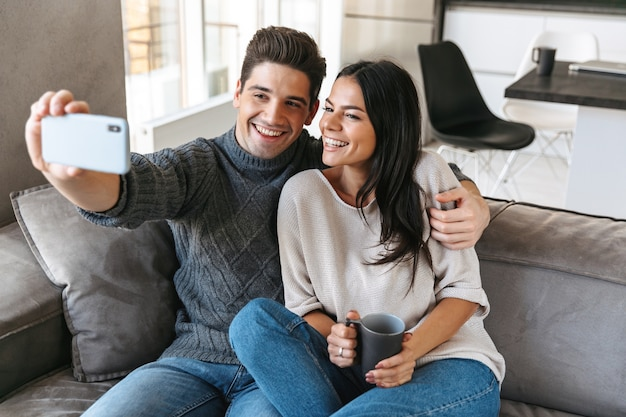 Happy young couple sitting on a couch at home, drinking tea