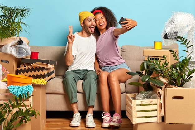 Happy young couple sitting on the couch surrounded by boxes