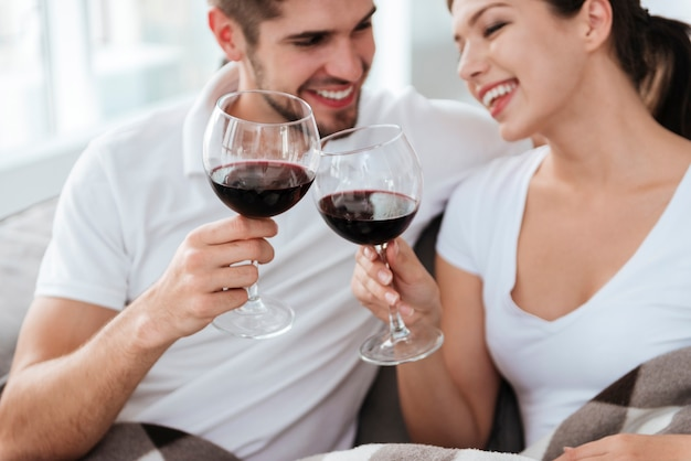 Happy young couple sitting and drinking wine at home