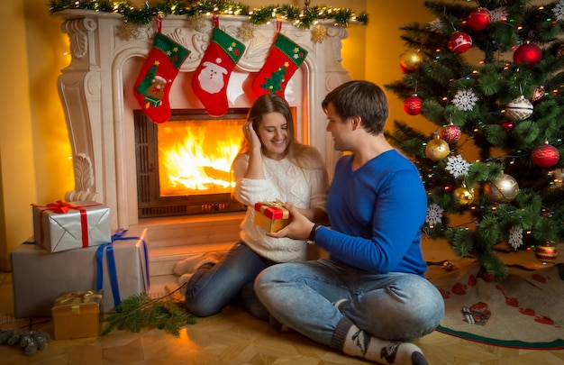Happy young couple sitting on floor at burning fireplace and giving christmas presents