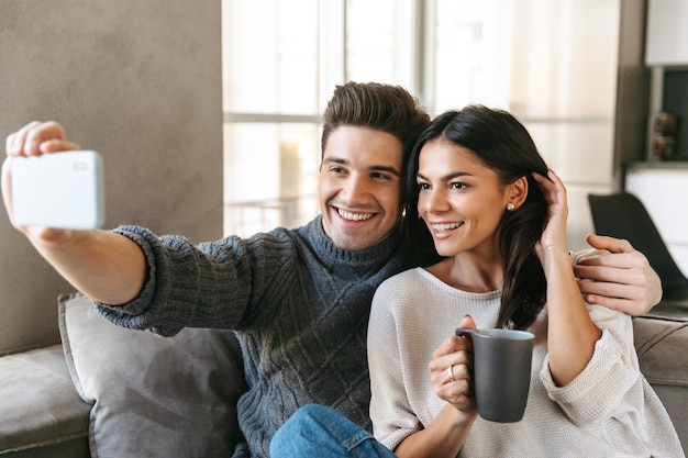Счастливая молодая пара, сидя на диване у себя дома, пьет чай