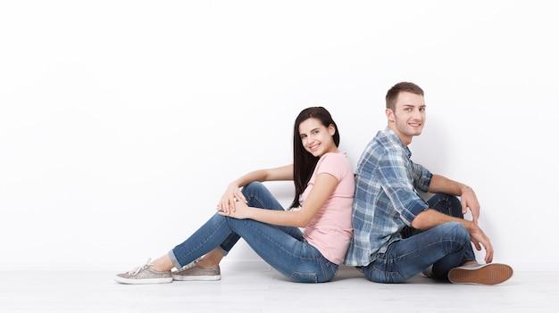 바닥에 앉아 웃고 있는 행복한 젊은 커플