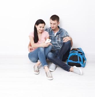 바닥에 앉아 스마트폰을 보고 사용하는 행복한 젊은 커플