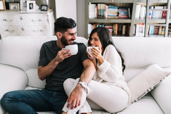 Happy young couple sitting on sofa holding white coffee cup