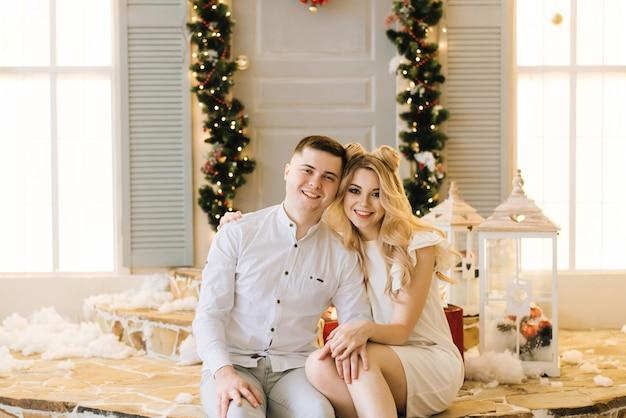 Счастливая молодая пара, сидя на крыльце дома украшены на рождество