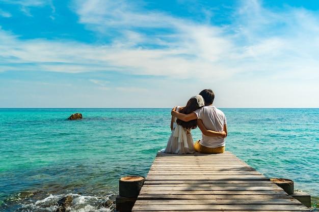 Happy young couple sitting on a wood bridge and sea beach at koh munnork island, rayong, thailand